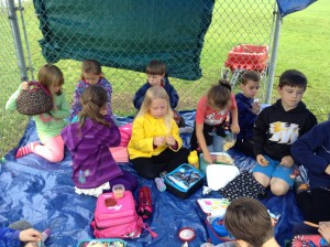 Students worked together to build a shelter using tarps, ropes and clothespins along side the baseball diamond so that we had a cozy place to read, sing and eat our snacks when it rained!